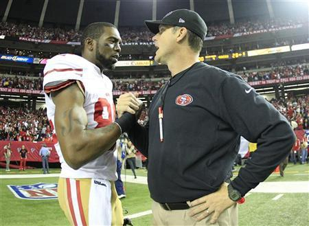 San Francisco 49ers wide receiver Randy Moss (L) shakes hands with head coach Jim Harbaugh after the 49ers defeated the Atlanta Falcons to win the NFL NFC Championship football game in Atlanta, Georgia January 20, 2013. REUTERS/Sean Gardner