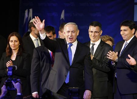 Israel's Prime Minister Benjamin Netanyahu waves to supporters as he stands with his party members at the Likud-Yisrael Beitenu headquarters in Tel Aviv January 23, 2013. REUTERS/Nir Elias