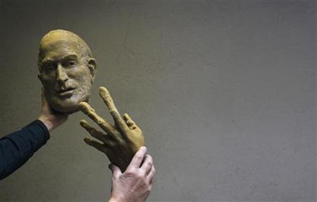 Hungarian sculptor Erno Toth holds up a face and a hand of a wax model for a new bronze statue of late Apple co-founder Steve Jobs in Budapest November 18, 2011. REUTERS/Laszlo Balogh/Files