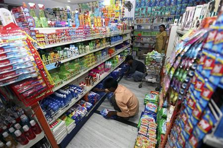 Workers arrange consumable goods as a customer (back) shops at a grocery store in Lucknow July 6, 2009. REUTERS/Pawan Kumar/Files