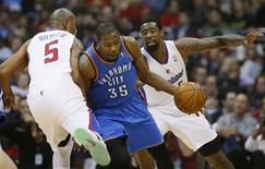 Oklahoma City Thunder's Kevin Durant (C) is fouled by Los Angeles Clippers Caron Butler (L) as the Clippers DeAndre Jordan looks on during their NBA basketball game in Los Angeles, January 22, 2013. REUTERS/Lucy Nicholson