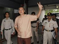 "Somyot Prueksakasemsuk (C), editor of ""Voice of the Oppressed"", a magazine devoted to self-exiled former Prime Minister Thaksin Shinawatra, gestures as he arrives at the criminal court in Bangkok January 23, 2013. REUTERS/Chaiwat Subprasom"