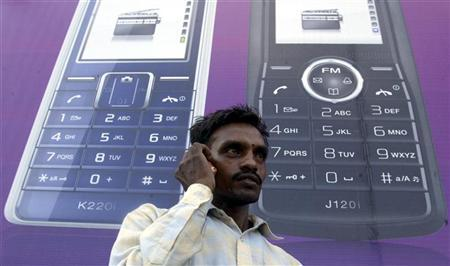 A man speaks on a mobile phone in front of a billboard in the northern Indian city of Chandigarh August 24, 2007. REUTERS/Ajay Verma/Files