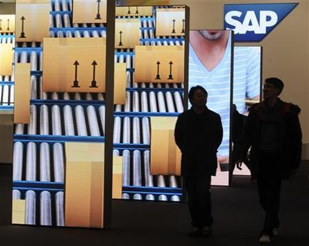 People are pictured beside screens at the booth of German company SAP during preparations at the CeBit computer fair in Hanover, March, 4, 2012. REUTERS/Fabian Bimmer