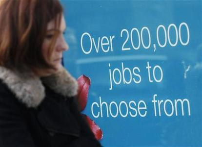 A woman passes an advertisement in the window of a recruitment centre in London December 14, 2011. REUTERS/Luke MacGregor