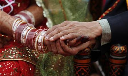 A couple take their wedding vows during their wedding ceremony in Ahmedabad January 23, 2011. REUTERS/Amit Dave/Files