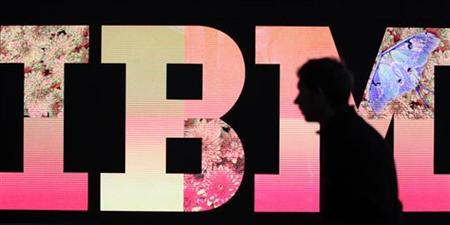 A man passes by an illuminated IBM logo at the CeBIT computer fair in Hanover February 27, 2011. The world's largest IT fair CeBIT opens its doors on March 1 and runs through March 5. REUTERS/Tobias Schwarz
