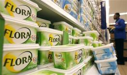 A worker scans barcodes by a chiller cabinet of Flora margarine at a Sainsbury's supermarket in London February 6, 2008. Flora is a brand owned by consumer products company Unilever. REUTERS/Luke MacGregor