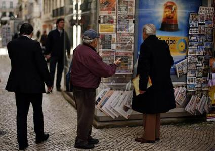 Men look at newspapers at a kiosk in downtown Lisbon January 23, 2013. REUTERS/Rafael Marchante