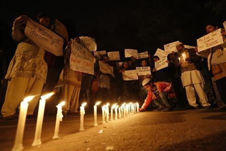 A boy places a candle as demonstrators hold placards during a candlelight march for a gang rape victim, who was assaulted in New Delhi January 16, 2013. REUTERS/Adnan Abidi