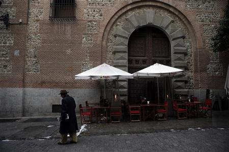 A man walks past the empty terrace of a restaurant in central Madrid January 8, 2013. REUTERS/Susana Vera