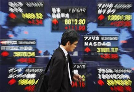 A man uses a mobile phone in front of an electronic board displaying market indices from around the world, outside a brokerage in Tokyo October 17, 2012. REUTERS/Issei Kato