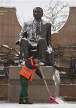 Дворник подметает площадку перед памятником первому президенту Казахстана Нурсултану Назарбаеву в Алма-Ате 30 ноября 2012 года. Назарбаев потребовал ускорить отмену действующего четыре года моратория на разработку недр и обвинил местные кланы в попытке удержать контроль над сырьевыми богатствами. REUTERS/Shamil Zhumatov