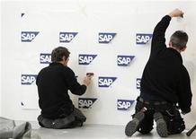 Foto de archivo de unos trabajadores montandon un panel con logos de SAP en el centro de exhibiciones CeBIT en Hannover, Alemania, feb 27 2010. El grupo alemán de software comercial SAP dijo que el crecimiento de los ingresos por software y servicios relacionados se desaceleraría a entre 11 y 13 por ciento este año, respecto de un 17 por ciento en 2012, mientras los clientes gastan menos en tecnología en medio de la incertidumbre económica. REUTERS/Thomas Peter