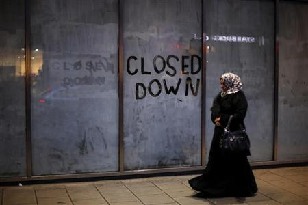 A woman walks past a closed down business in central London, December 5, 2012. REUTERS/Andrew Winning