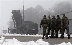 "Soldiers of the German armed forces Bundeswehr walk next to a PAC-3 launcher of a ""Patriot"" missile battery during a media rehearsal in the north German village of Warbelow December 18, 2012. REUTERS/Tobias Schwarz (GERMANY - Tags: POLITICS MILITARY CIVIL UNREST)"