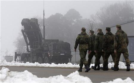 Soldiers of the German armed forces Bundeswehr walk next to a PAC-3 launcher of a ''Patriot'' missile battery during a media rehearsal in the north German village of Warbelow December 18, 2012. REUTERS/Tobias Schwarz (GERMANY - Tags: POLITICS MILITARY CIVIL UNREST)