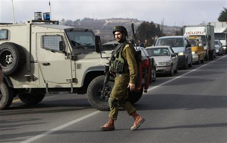 An Israeli soldier walks in front of a military vehicle blocking traffic on a road near the scene of a shooting in al-Arroub refugee camp near the West Bank city of Hebron January 23, 2013. REUTERS/Ammar Awad