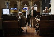 La bolsa española cerró el miércoles con un leve descenso motivado por recogidas de beneficios tras la reciente racha alcista, en un mercado que aún está pendiente de las negociaciones sobre el techo de deuda en Estados Unidos. En la imagen, unos operadores en la Bolsa de Madrid, el 6 de julio de 2012. REUTERS/Andrea Comas