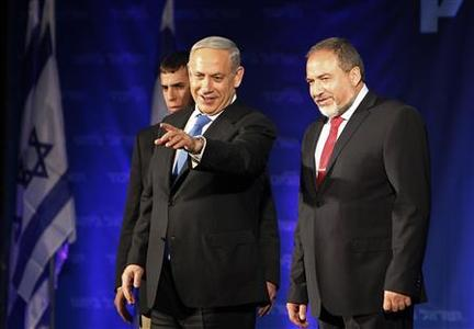 Israel's Prime Minister Benjamin Netanyahu (C) and former foreign minister and head of the Yisrael Beitenu party Avigdor Lieberman (R) look at supporters at the Likud-Yisrael Beitenu headquarters in Tel Aviv January 23, 2013. REUTERS/Nir Elias