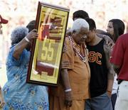 Family members hold up a No. 55 jersey as part of a ceremony held in memory of the late former USC Trojans, San Diego Chargers and NFL linebacker Junior Seau after the first quarter of the NCAA football game between the USC Trojans and the Hawaii Warriors in Los Angeles September 1, 2012. REUTERS/Danny Moloshok