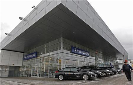 A man walks past cars for sale on display outside the Hyundai showroom in St.Petersburg January 15, 2013. REUTERS/Alexander Demianchuk