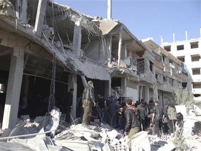 Free Syrian Army fighters and residents are seen near buildings damaged after what activists say were missiles fired by Syrian Air Force fighter jets loyal to Syria's President Bashar al-Assad, in Erbeen, near Damascus January 21, 2013, in this picture provided by Shaam News Network. REUTERS/Maawia Al-Naser/Shaam News Network/Handout