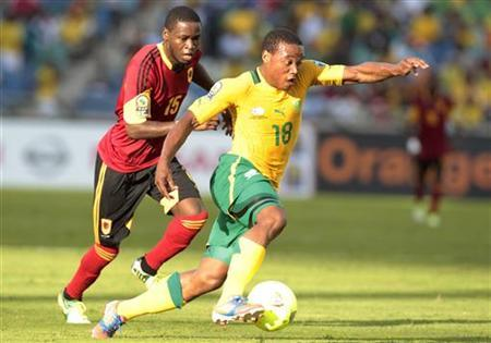 South Africa's Thuso Phala (18) dribbles the ball past Angola's Miguel (15) during their African Nations Cup Group A soccer match at the Moses Mabhida stadium in Durban, January 23, 2013. REUTERS/Rogan Ward