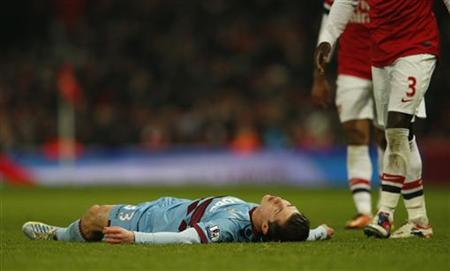 West Ham's Daniel Potts lies on the pitch after he was injured during their English Premier League soccer match against Arsenal at Emirates Stadium in London January 23, 2013. REUTERS/Eddie Keogh