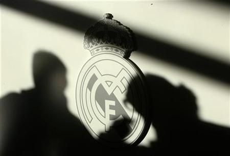 Shadows of reporters are seen on Real Madrid's logo during a news conference in Madrid December 9, 2008. REUTERS/Andrea Comas