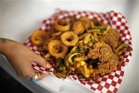 A woman holds a plate of fried food at the Los Angeles County Fair in Pomona, California September 5, 2012. REUTERS/Lucy Nicholson