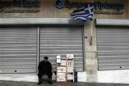 A lottery ticket vendor sits outside an Emporiki Bank branch in Athens December 30, 2012. REUTERS/Yorgos Karahalis