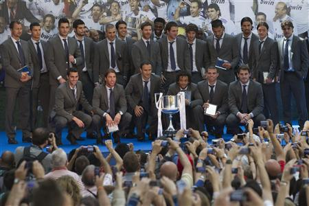 Real Madrid soccer players pose with the King's Cup trophy after a meeting with Madrid's Mayor Alberto Ruiz-Gallardon, at Madrid's Town Hall, in this May 11, 2011 file photograph. Madrid, who won the Spanish league last May for the 32nd time, have defied Spain's financial crisis to become the first club in any sport to generate more than 500 million euros ($664 million)in annual revenues, Deloitte said in its annual Football Money League for 2011-12. REUTERS/Juan Medina/Files
