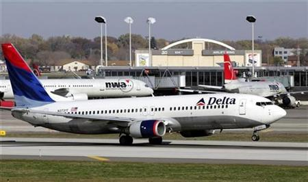 A Delta Air Lines jet takes off past a Northwest Airline jets parked at gates at the Minneapolis St.Paul International Airport in Minneapolis, Minnesota October 30, 2008. REUTERS/Eric Miller