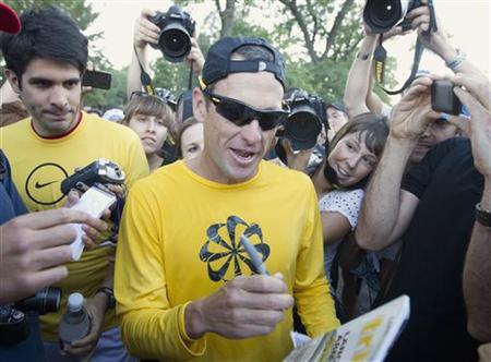 Lance Armstrong (C) signs autographs following a run with his fans at Mount Royal park in Montreal August 29, 2012. REUTERS/Christinne Muschi/Files