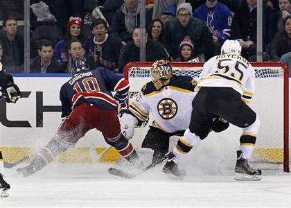 New York Rangers right wing Marian Gaborik (L) scores the game-winning goal against Boston Bruins goalie Tuukka Rask (C) in front of Bruins defenseman Johnny Boychuk in overtime period action during their NHL hockey game at Madison Square Garden in New York January 23, 2013. REUTERS/Adam Hunger