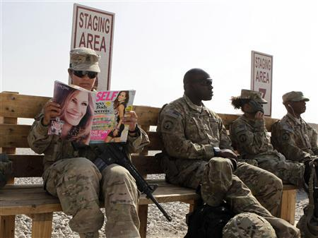 U.S. Army soldier SSG Norma Gonzales of 426 Civil Affairs Battalion reads a magazine while waiting to be ferried by a helicopter to different U.S. military bases in Kandahar, southern Afghanistan, in this October 11, 2012 file photo. REUTERS/Erik De Castro/Files