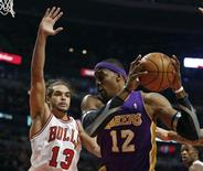 Chicago Bulls center Joakim Noah (13) defends against Los Angeles Lakers center Dwight Howard during the first half of their NBA basketball game in Chicago, Illinois January 21, 2013. REUTERS/Jeff Haynes