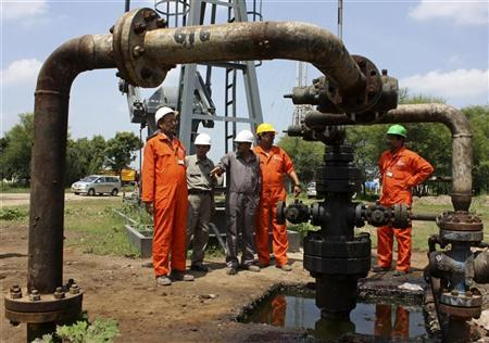 Engineers of Oil and Natural Gas Corp (ONGC) stand inside the Kalol oil field in Gujarat September 12, 2009. REUTERS/Amit Dave/Files