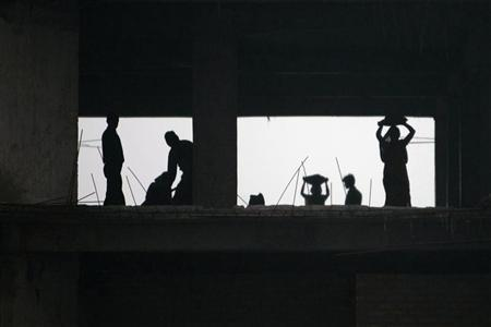 Construction workers are silhouetted as they work at a high rise building in Kolkata January 25, 2008. REUTERS/Parth Sanyal/Files