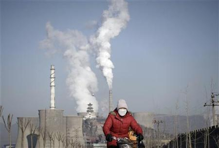 A woman wearing a mask rides past smoking chimneys and cooling towers of a steel plant in Beijing, January 17, 2013. REUTERS/Suzie Wong