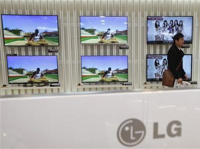 A customer talks in front of LG 3D TV sets which are made with LG Display flat screens, at a store in Seoul January 23, 2013. REUTERS/Kim Hong-Ji