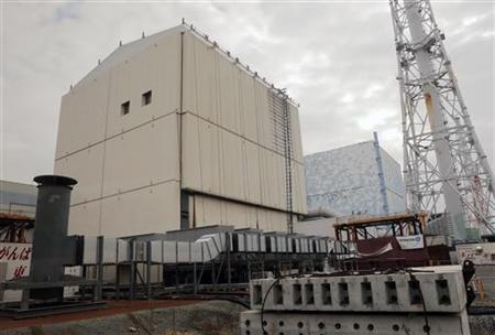 The unit No.1 (L) and No. 2 reactor building of the tsunami-crippled Fukushima Daiichi nuclear power plant are seen through a window in a bus while Japan's new Prime Minister Shinzo Abe inspects the nuclear power plant power plant in Fukushima Prefecture December 29, 2012. REUTERS/Itsuo Inouye/Pool