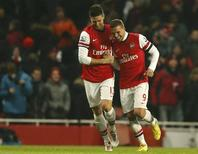 Lukas Podolski (à droite) félicitant Olivier Giroud, auteur d'un doublé pour Arsenal contre West Ham, en match décalé de la 23e journée de Premier League. Les Gunners l'ont emporté 5-1 et se maintiennent au sixième rang avec 37 points, à 19 longueurs du leader Manchester United. /Photo prise le 23 janvier 2013/REUTERS/Eddie Keogh