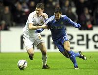 Ben Davies de Swansea (à gauche) à la lutte avec Eden Hazard de Chelsea, en demi-finale retour de la Coupe de la League anglaise. Vainqueur 2-0 à l'aller, le club gallois a tenu les Blues en respect 0-0 et obtient ainsi sa première finale dans la compétition. /Photo prise le 23 janvier 2013/REUTERS/Rebecca Naden