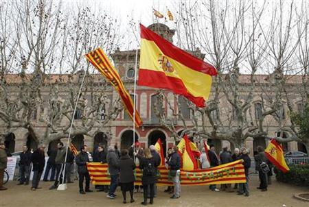 People holding Spain's and Catalunya's flags protest against the holding of a referendum on separation from Spain in front of Catalunya's Parliament in Barcelona, January 23, 2013. REUTERS/Albert Gea