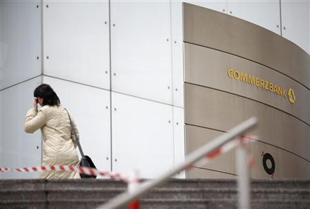 A woman walks next to a sign in front of Germany's Commerzbank headquarters in Frankfurt January 18, 2013. Commerzbank, Germany's No.2 bank is to present new information on planned job cuts. REUTERS/Lisi Niesner