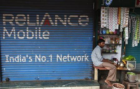 A street vendor sells his goods beside a Reliance mobile phone store in Mumbai June 8, 2010. REUTERS/Reinhard Krause/Files