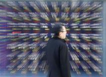 Tokyo, un passante davanti a un tabellone elettronico con l'andamento dei titoli di Borsa lo scorso 18 gennaio. REUTERS/Kim Kyung-Hoon