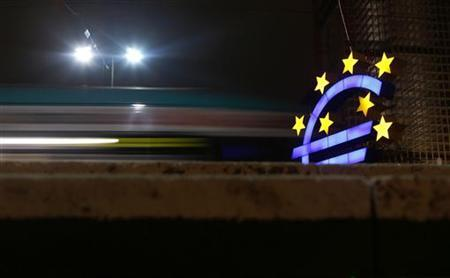 The illuminated euro sign is seen in front of the headquarters of the European Central Bank (ECB) as a tram passes by in Frankfurt late evening, January 8, 2013. REUTERS/Kai Pfaffenbach
